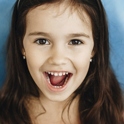 A little girl with long, dark hair smiling with her mouth open after seeing her dentist near Aledo, TX