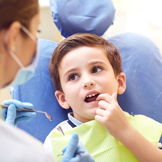 A young boy pointing to a bothersome tooth while a dentist prepares to check it