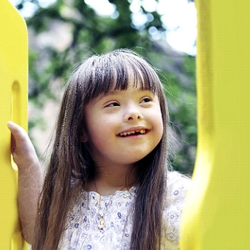 A young girl with special needs smiles while playing on a playground