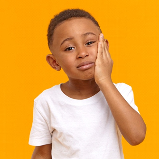 A young boy wearing a white t-shirt and holding his cheek in pain