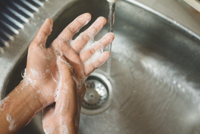 a person washing their hands with soap and water