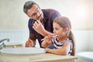 Father teaches daughter toothbrushing skills as recommended by Willow Park children's dentist